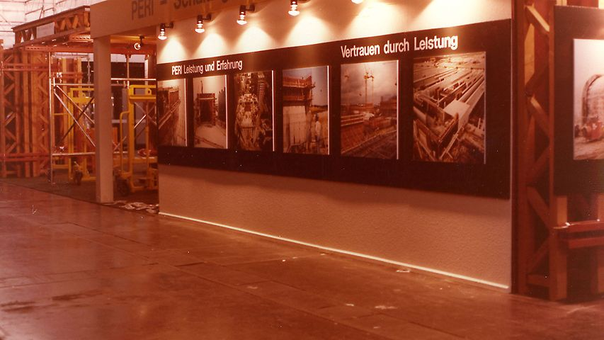 The booth 1977 is built with T70 girders. Project posters show the competence of PERI.