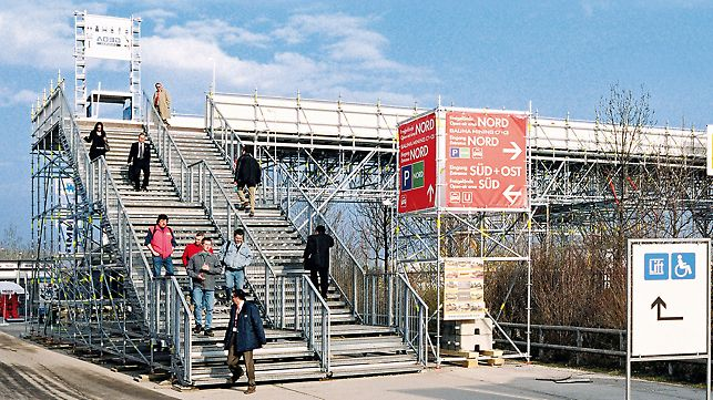 Solution for a trade fair: stairway leading to a pedestrian bridge over a multi-lane road with separate routes for up and down.