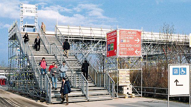 Lösung für eine Messe: Treppe zu einer Fußgängerbrücke über eine mehrspurige Straße mit getrennten Bereichen für den Auf- und Abgang.