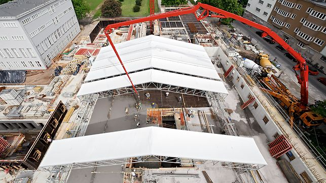 During shell construction, the PERI UP weather-protection roof offers temporary protection against rain, snow or heat. The elements can be moved by hand. In the motor-operated version, the individual segments of roof sheeting can be easily coiled up or uncoiled; a heated version reduces the snow load in winter.