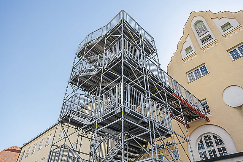 During reconstruction work, this 14 m high stair tower serves as an emergency escape route. VARIOKIT system components support the transfer to the building.