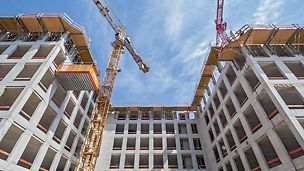 """Blick von unten auf die Faltbühnen FB 180 sowie die RCS MP Ausfahrbühne von PERI am Rohbau des MK 4 """"Friends"""", Stadtquartier am Hirschgarten, München"""