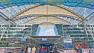 Zastřešení na mnichovském letišti: Výměna membrán probíhala za plného provozu letiště. O nejvyšší míru bezpečnosti se kromě lešení umístěného pod střechou a opatřeného ochrannými sítěmi postarala velkoplošná ochranná střešní konstrukce na výšku celé plochy fóra.