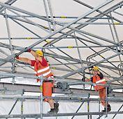 Les éléments de toiture se déplacent dans la direction longitudinale à l'aide de roues, ce qui permet par exemple de livrer des matériaux avec une grue.