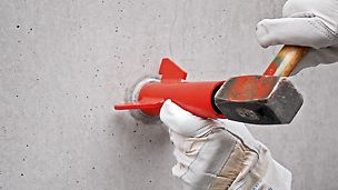 Tap the concrete cone flush with the cone gauge.