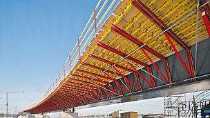 Tanto para puenteos cortos sobre vías, autopistas o carreteras secundarias, como para obras más grandes, la consola de voladizo permite soluciones rentables y racionales. Sus ventajas decisivas son el rápido montaje, el peso propio reducido y su fijación con piezas de anclaje estándar.