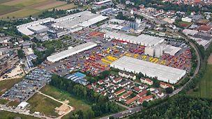 Luftaufnahme vom Firmengelände der PERI GmbH in Weißenhorn. Zwischen den großen Gebäuden sieht man die roten und gelben Schalungs- und Gerüstsysteme, die auf den Lagerflächen gestapelt wurden.