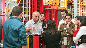PERI Experte erklärt den umstehenden Seminarteilnehmern die Produkte im Praxistraining.