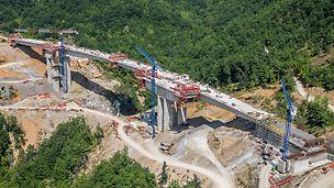 În prima secțiune, prin regiunea muntoasă din vestul Macedoniei de Nord, noua autostradă traversează un total de 14 viaducte. Pe o lungime de aproximativ 10 km, 4 000 000 m³ de pământ trebuiau să fie excavate cu 150 000 de tone de beton și 15 000 de tone de armare ulterior prelucrate.