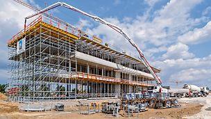 Un haut niveau de sécurité et des séquences de sous-assemblage rapides ont pu être obtenus tout particulièrement grâce à la passerelle SKYDECK sur le bord du plafond et aux niveaux de travail intégrés sur l'échafaudage de support PERI UP.