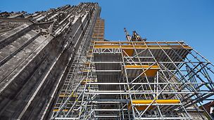 PERI UP se fixeaza pe Catedrala Ulm - până la 71 m înălțime - pentru lucrările ample de renovare. O platformă intermediară înaltă de 7 m oferă o posibilă locație de depozitare a noilor pietre.