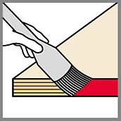 Picture of a hand that coats the edges of a formwork panel with a brush in order to illustrate the sealing of formwork panels.