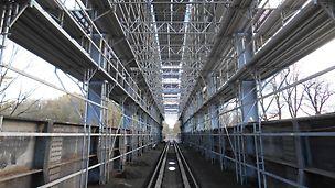 Železniční vlečka Biocel Paskov: Přizpůsobené modulové lešení PERI UP Rosett Flex pro oblouky a výztuhy vrchní části mostu se zachováním průjezdného profilu trati.
