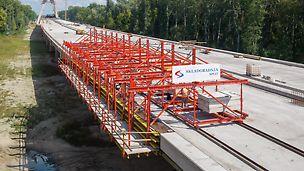 Auf dem Brückenüberbau verfahrbarer Wagen, der keine Verankerung im Bauwerk benötigt.