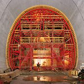 Tunnel bypass Flüelen, Switzerland - The special support und moving construction comprised of elements from the PERI tunnel waler system which adapted exactly to each cross-section. The complete formwork unit could be moved on rails from section to section using pulling equipment supplied by the contractors. Due to economic reasons, setting and stripping were done mechanically.