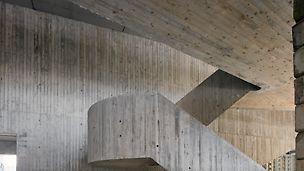 Les architectes ont conçu les escaliers et la passerelle du foyer en béton apparent entièrement coulé sur place.