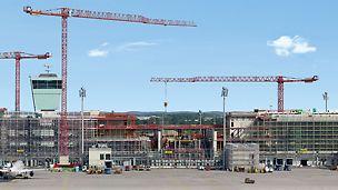 Satellitenterminal Flughafen München, Deutschland - Der 600 m lange, neue Satellitenterminal am Flughafen München befindet sich inmitten des Flugfelds, es umschließt den Vorfeldtower und gründet auf der vorhandenen Gepäcksortieranlage. Das Bauen im laufenden Betrieb ist eine enorme Herausforderung für alle Projektbeteiligten.