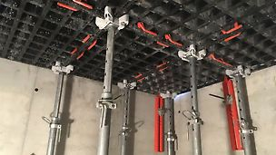 Punainen DUO-tukipalkki toimii jäykisteenä ankkuroiden holvimuotin kiinni seinään.