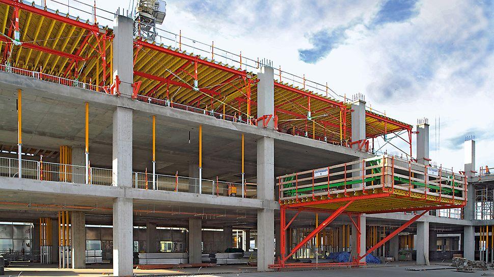 Klinika South Health Campus: Výsuvná lávka ze systémových dílů PERI slouží k přemístění stopních stolů do dalšího podlaží.