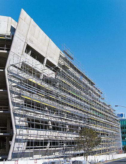 PERI UP Rosett fasadna skela optimalno se prilagođava skoro svakoj liniji zgrade – kao npr. ovoj fasadi, koja je prelomljena na nekoliko mesta. Time se postiže bezbedan pristup radnim površinama.