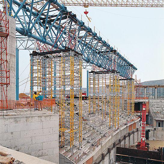 Schwerathlethik-Stadion, Athen, Griechenland - Nach der Fixierung des 72 m langen Stahl-Fachwerkträgers werden die drei Traggerüsttürme in wirtschaftlichen Umsetzeinheiten mit dem Kran zum nächsten Einsatz gebracht.