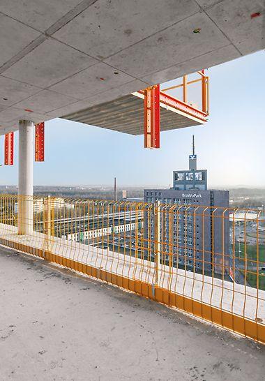 Blick aus einer Etage eines Rohbaus, in der der gelbe PERI PROKIT Seitenschutz installiert wurde und die MP Ausfahrbühne von der Etage darüber zu sehen ist.