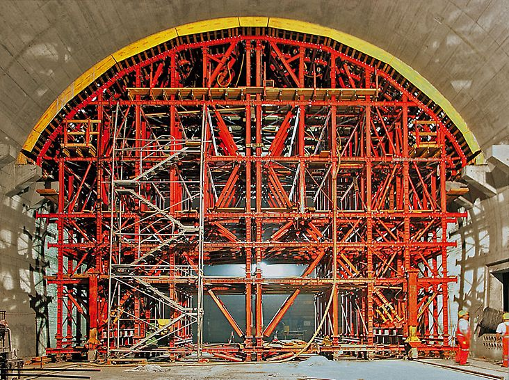 Lötschberg Tunnel, Mitholz, Switzerland - In the second stage, the formwork carriage was supplemented with the arched formwork. The formwork was raised and lowered by means of four hydraulic drive components.
