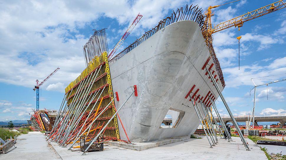 Za izradu zakrivljenih, kosih zidova koriste se specijalno projektovani elementi VARIO GT 24 oplate zidova, koji se unapred montiraju i isporučuju na gradilište. Oplata zidova od drvenih nosača optimalno se prilagođava kompleksnoj formi objekta i zahtevanom izgledu vidljivog betona, uključujući raspored fuga i mesta ankerovanja. Rezultat govori sam za sebe.