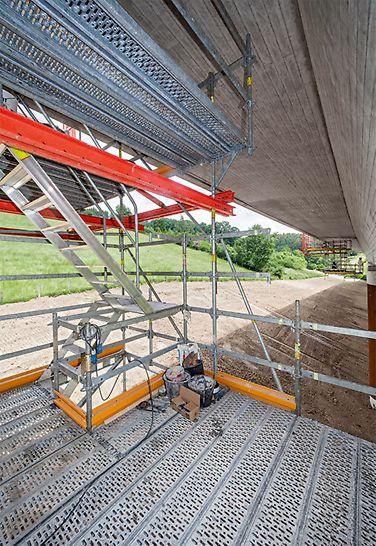 Die abgehängten und bis zu 5 m auskragenden Arbeitsplattformen wurden so dimensioniert, dass die komplette Brückenuntersicht im Kragarmbereich zugänglich und zu bearbeiten war. Eine integrierte Gerüsttreppe sorgte für die schnelle und komfortable Erreichbarkeit der unterschiedlichen Arbeitsebenen.