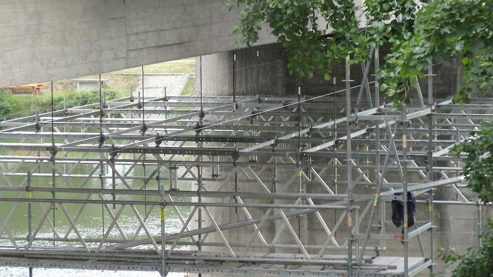 SO 201 Rekonštrukcia mosta, lávky pri starom moste na Ostrov, Trenčín - Zavesená pracovná podlaha spĺňala požiadavky zhotoviteľa pre návrh a montáž bezpečného pracovného lešenia v neštandardných podmienkach stavby. Most ostal počas celej rekonštrukcie v prevádzke.