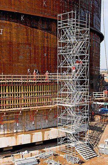PEscaleras de andamio dobles para la construcción de un nuevo tanque de gas líquido. Las barandillas en las zancas extriores y centrales permiten transitar las escaleras con seguridad