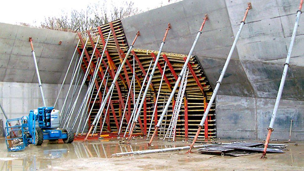 Topsportschool Leonardo Lyceum Wilrijk - De onderste bekisting van de wand met 2 knikpunten werd gebruikt als tijdelijke ondersteuning van de eerste fase. Vervolgens werd hierboven de 2de fase gestort met een herbruikbare bekisting.