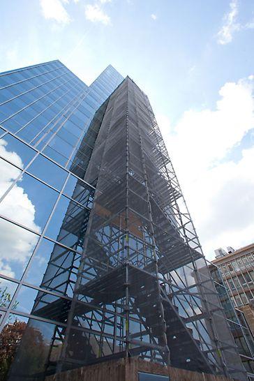 PERI Gerüsttreppen als temporäre Fluchttreppen: Platzsparender PERI UP Flex Treppenturm 100  als temporäre Nottreppe an einer Hochhaus-Glasfassade in Frankfurt am Main.