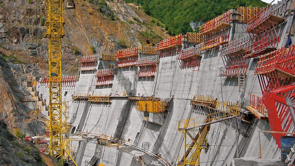 Na koruně této přehradní hráze obloukovitého tvaru s délkou 280 m a proměnlivým sklonem přenášejí konzoly vysoké zatížení.