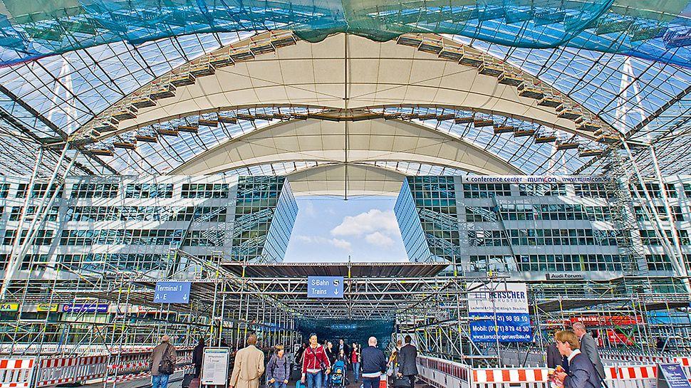 Forumdach Flughafen München, Deutschland - Der Membranaustausch erfolgt unter laufendem Flughafenbetrieb. Für ein Höchstmaß an Sicherheit sorgt zusätzlich zu den unterhalb der eingerüsteten Dachfelder angebrachten Schutznetzen eine großflächige Schutzdachkonstruktion auf Höhe der Forumfläche.