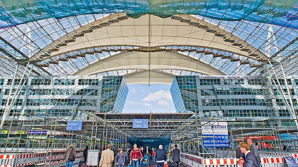 Forum roof Munich Airport, Germany - Replacing the membrane was carried out during ongoing daily airport operations. Maximum safety was ensured through a large-area protective roof construction installed at the height of the forum area in addition to the safety netting underneath the scaffolded roof sections.