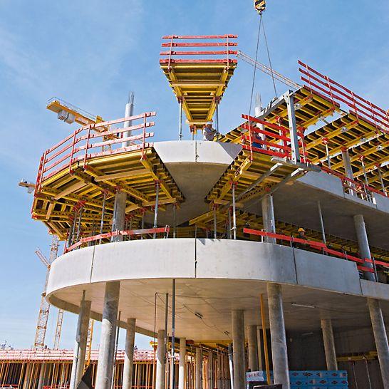 ADAC Zentrale, München, Deutschland - Zum schnellen und sicheren Schalen der geschwungenen Geschossdecken werden mietbare Modul- und trapezförmige Maßtische inklusive der Absturzsicherungen umgesetzt.