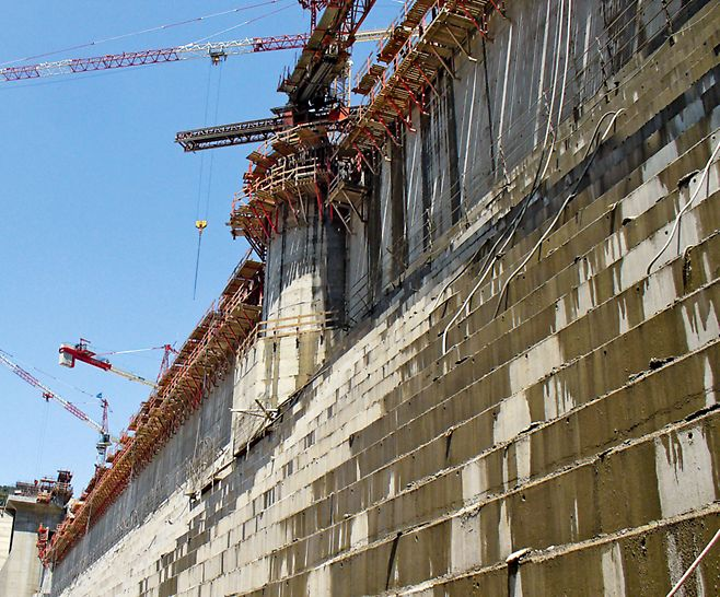 Přehrada Koudiat Acerdoune: Při betonáži u jednostranného šplhavého systému SKS bylo zatížení tlakem čerstvého betonu odváděno prostřednictvím V-závor a tlakových vzpěr konzolami do kotev pro lešení.