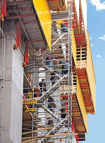 PERI UP Rosett Stair Alu 64: Stair tower with alternating staircase units under a self-climbing RCS rail climbing system with entrances into the building.