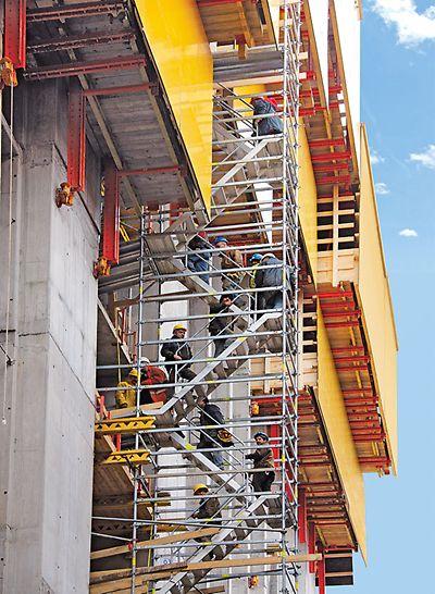 PERI UP Rosett Treppe Alu 64: Gegenläufige Gerüsttreppe unter einem selbstkletternden RCS Schienenklettersystem mit Zugängen in das Gebäude.
