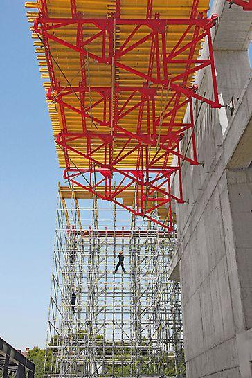 Sportovní aréna Lora: Pracovní lávky široké 7m o délce 58 m, nesené opěrnými rámy PERI pootočenými do vodorovné polohy.