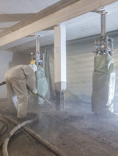 Worker refurbishes a reinforced concrete support with the SPCC dry-mix shotcreting procedure while PERI UP heavy-duty props provide support for the slab.