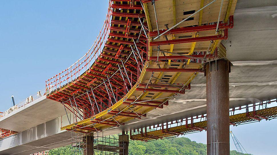 VARIOKIT φορείο σκυροδέτησης πεζοδρομίων γεφυρών: Η μετακίνηση του φορείου γίνεται με τρόπο οικονομικό και σύμφωνα με τις απαιτήσεις του εργοταξίου μέσω χαλύβδινων προφίλ. Κατά κανόνα, δεν απαιτείται αγκύρωση στα δομικά στοιχεία της κατασκευής και οι οριζόντιες δυνάμεις μεταφέρονται μέσω τριβής.
