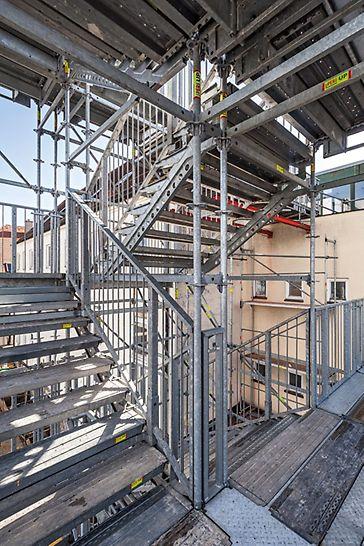 PERI Gerüsttreppen als temporäre Fluchttreppen: 14 m hoher PERI UP Public Treppenturm als temporärer Fluchtweg während Sanierungsmaßnahme im Gebäudeinnern.