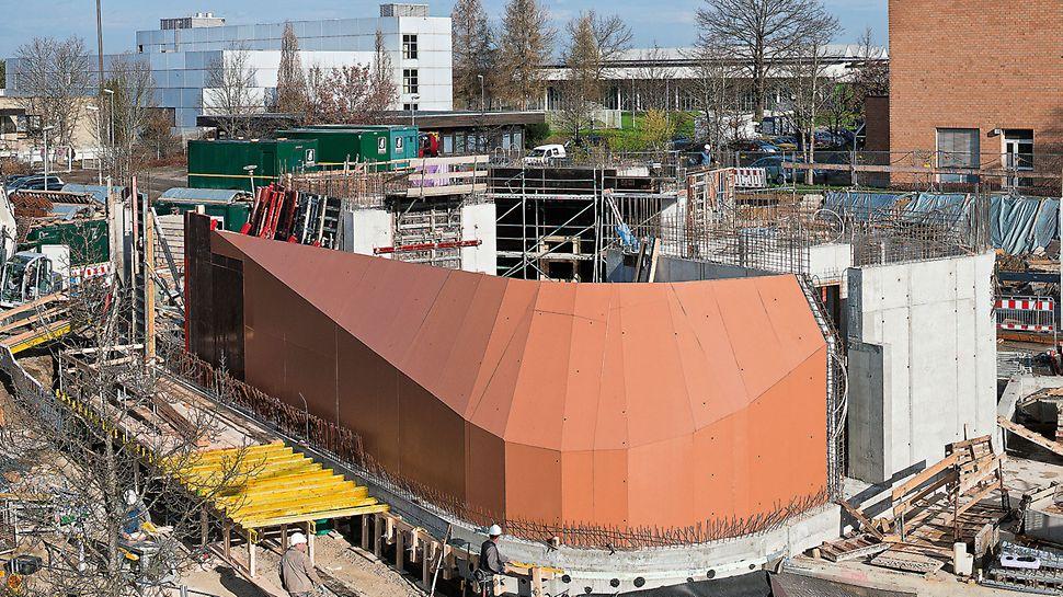 De zuidzijde van dit gebouw loopt door in een boogstraal; tegelijkertijd helt de wand op de begane grond 35° aan de binnenzijde.