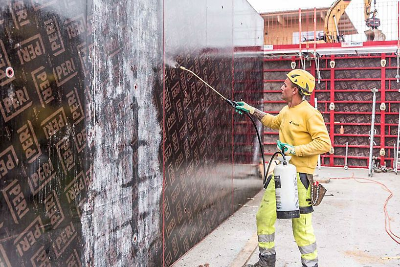 ein Arbeiter sprüht Öl auf die Schalung