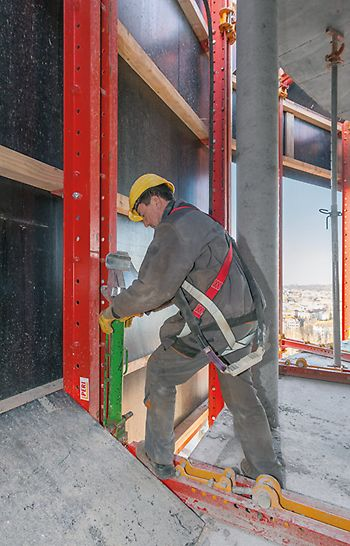 A worker, who positions the climbing rail and the climbing shoe on the RCS protection panel unit with a mobile hydraulic cylinder.