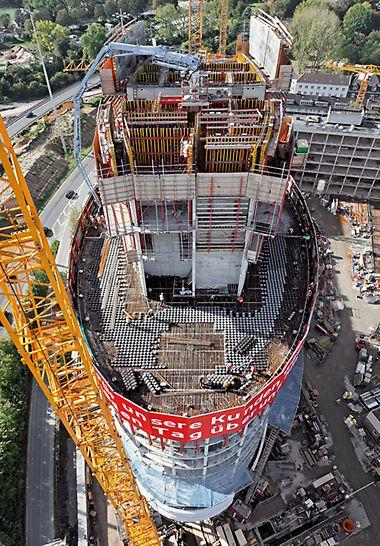 Luftaufnahme  des elliptisch geformten Büroturms der mithilfe  der PERI RCS und ACS Selbstklettertechnik nach oben wächst, die RCS Kletterschutzwand sichert die Absturzkanten der nachfolgend zu errichtenden Geschossdecken.