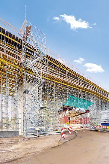 Přemostění železničního uzlu Krakov-Plaszóv: V krajních polích bylo podepření 207 m dlouhého viaduktu vyřešeno konstrukcí ze systému PERI UP Rosett Flex s průjezdem vytvořeným z vysokopevnostních podpěr HD 200. Díky systémovému modulu po 25 cm popř. 50 cm je možné přizpůsobit umístění sloupků flexibilně podle odváděného zatížení. Hliníkové schodiště ze systému PERI UP Rosett sloužilo pro bezpečný přístup na pracoviště.
