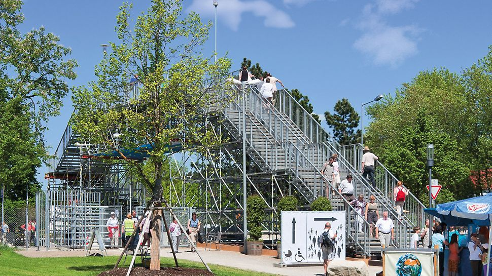 PERI UP Rosett Staircase Public: Solution for a trade fair: stairway leading to a pedestrian bridge which crosses a multi-lane road.